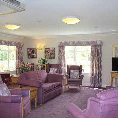 Room filled with purple furniture and a TV