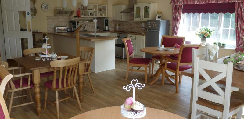 A kitchen area with tables and chairs with cakes on them